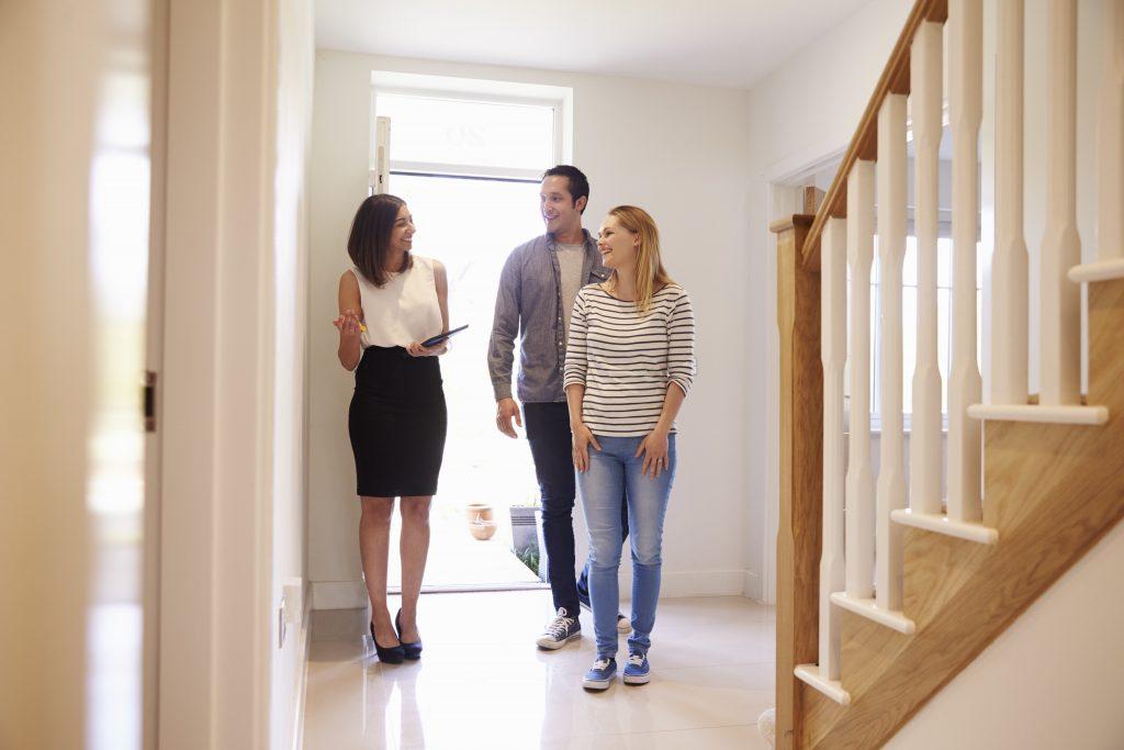 maklerin die junges paar immobilie zum verkauf zeigt